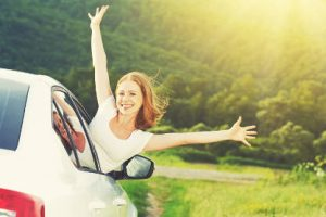 girl-leaning-out-of-car-window-on-raod-with-sunshine-and-fields